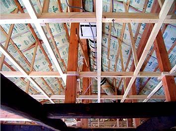 屋根、内側にも二重に断熱材グラスウールを施工する。最上部に温まった空気を床下へと吹き下ろし循環させるためのファンとダクトが見える