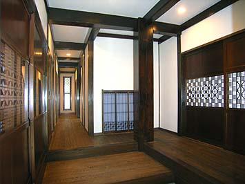 玄関ホール、建具の格子や組子が美しい。大黒柱や梁は古民家から解体移築した軸組みの古材セット