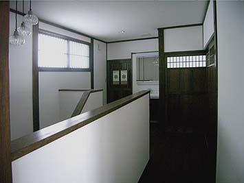 二階の階段室ホール、ドアや引戸に組み込んだ古建具が面白い。ガラスのペンダント式照明器具もセンスがいい