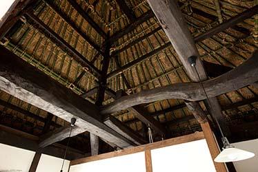 小屋を見上げると、たいへん太い梁に曲がりくねった小梁が巧みに組まれています。茅葺き屋根の下地の垂木竹が放射線状に並んできれいです