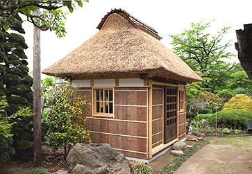 竣工外観 屋根は寄せ棟茅葺き、壁は杉皮の細竹押さえ