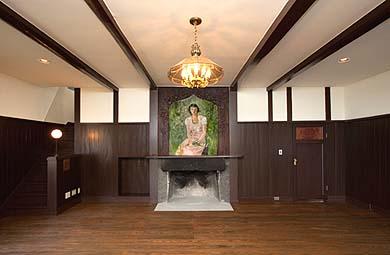 居間、12坪(24畳)の板の間、石造りの暖炉の上に若き麗人の肖像画あり
