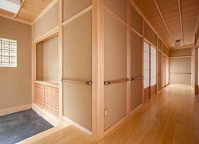 玄関から廊下を見る 玄関以外の床はもちろんバリアフリー、歩行用の手すりがぐるりと巡る
