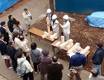 参加者に伝統工法の木組みの継ぎ手や仕口の説明をするスタッフ