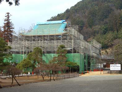 工事中 重層屋根の巨大建築を仮設の足場が覆う