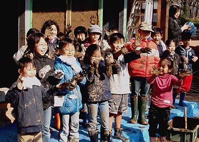 子供は泥んこ遊びが大好きです、真っ黒の手と満面の笑み。