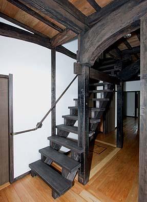 廊下奥より二階へと続く階段、柱からのびるチョウナ梁はたいへん個性的