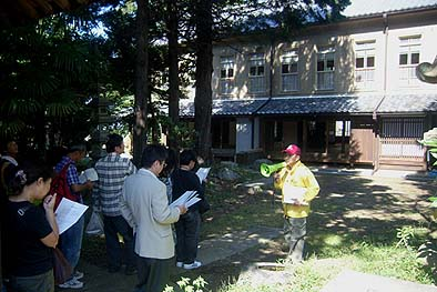 主屋前庭で市の担当者から説明を受ける見学者