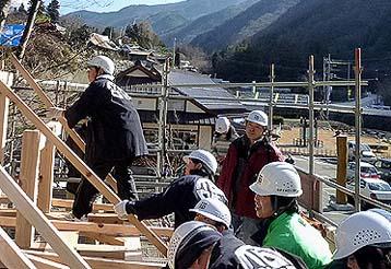 柱・梁と順番に組みあがって最後に屋根のタルキを架け渡すこども達